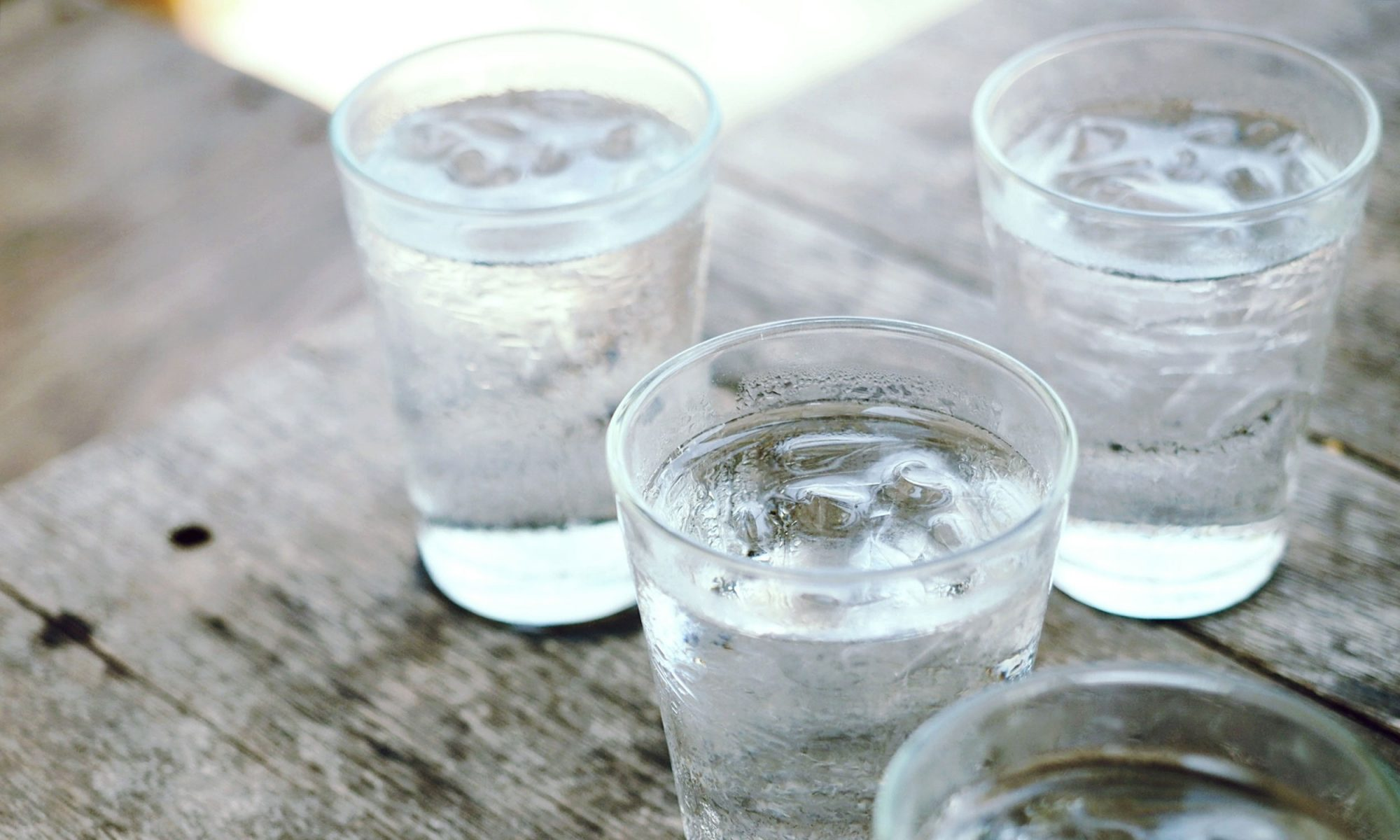 Four glasses of ice cold water on a wooden background