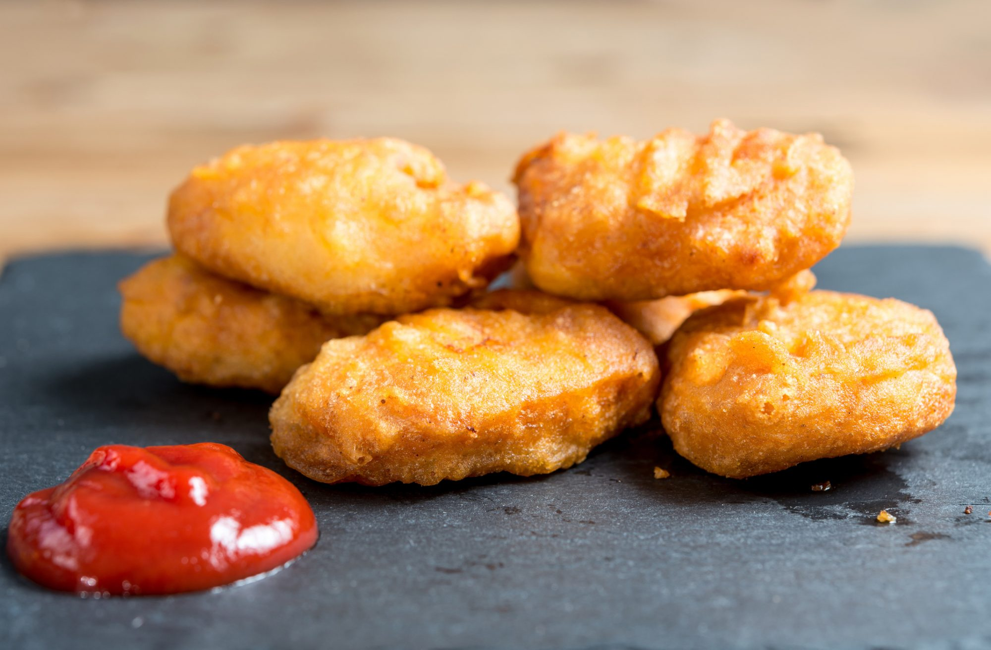 Close-Up Of Chicken Nuggets With Sauce On Granite Plate