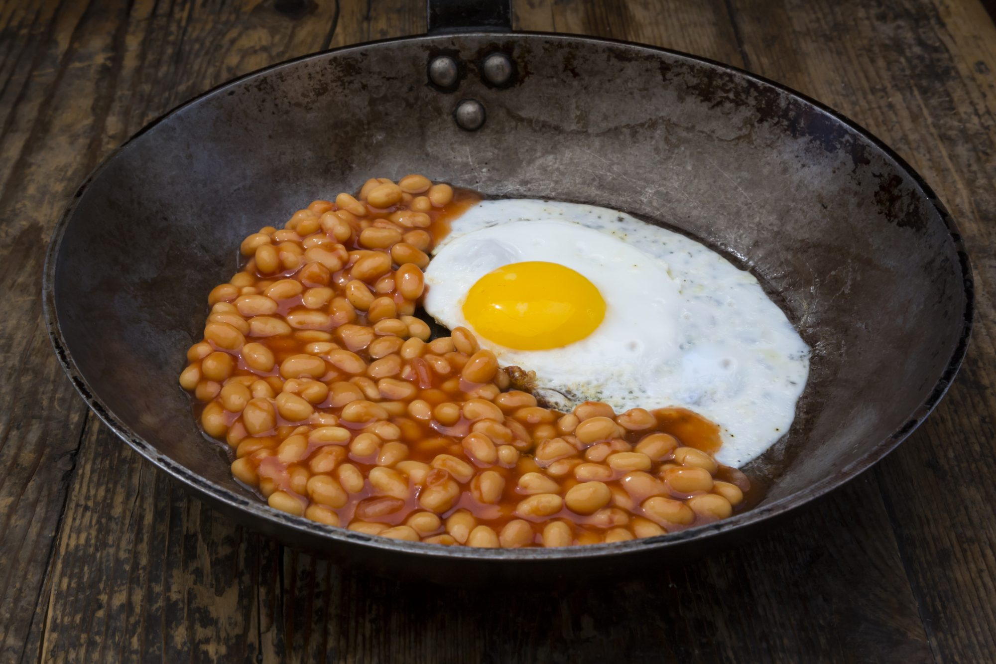 Fried egg and baked beans in frying pan on wood