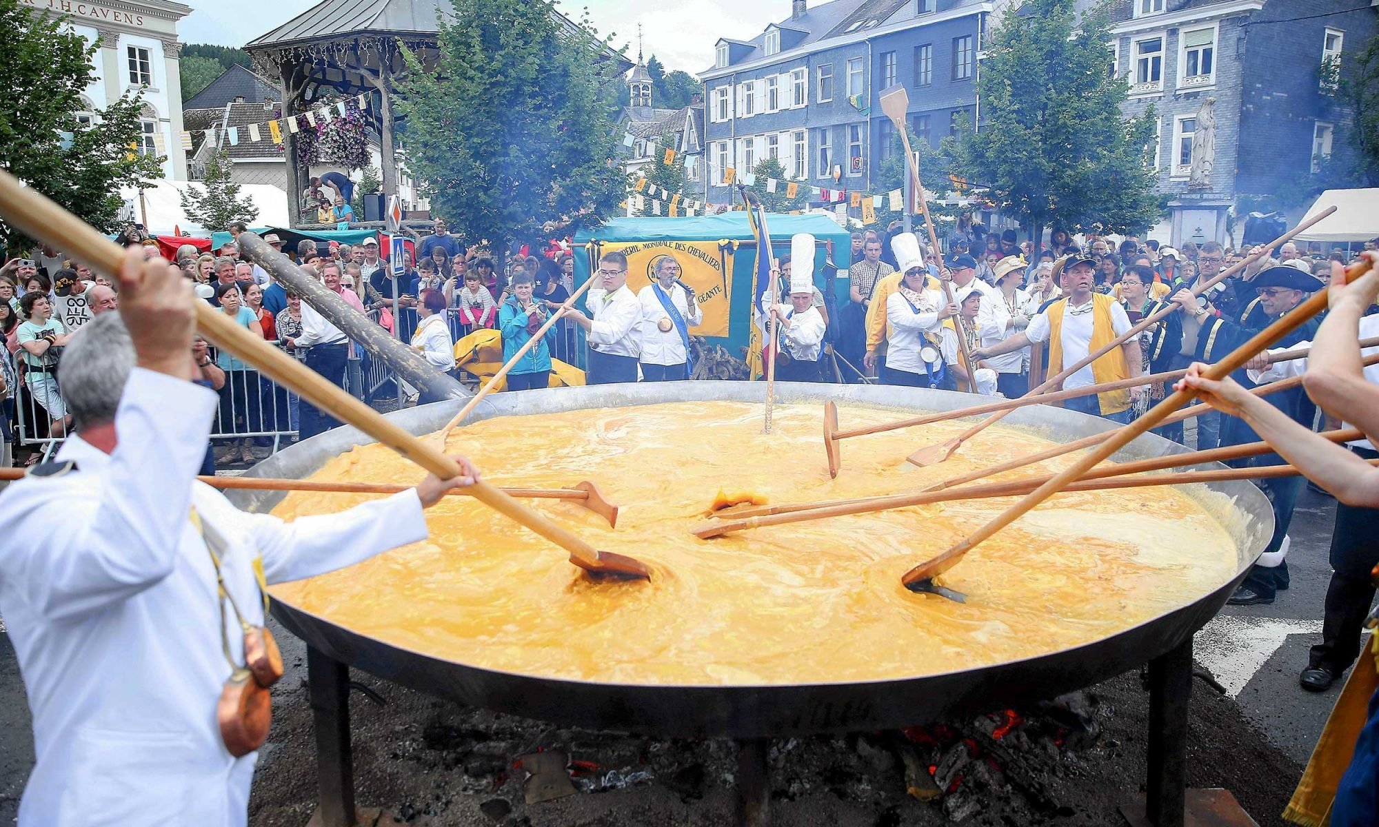 Men stirring giant omelet in pan over open flame
