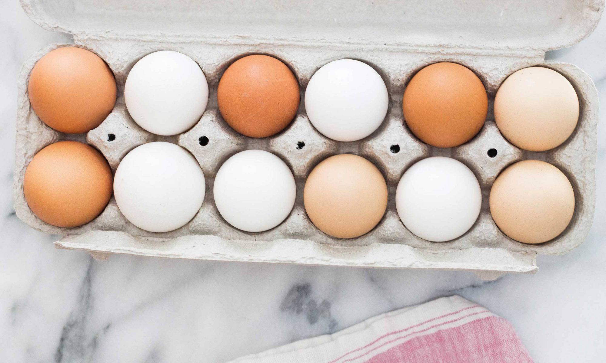 Dozen eggs in carton on marble top
