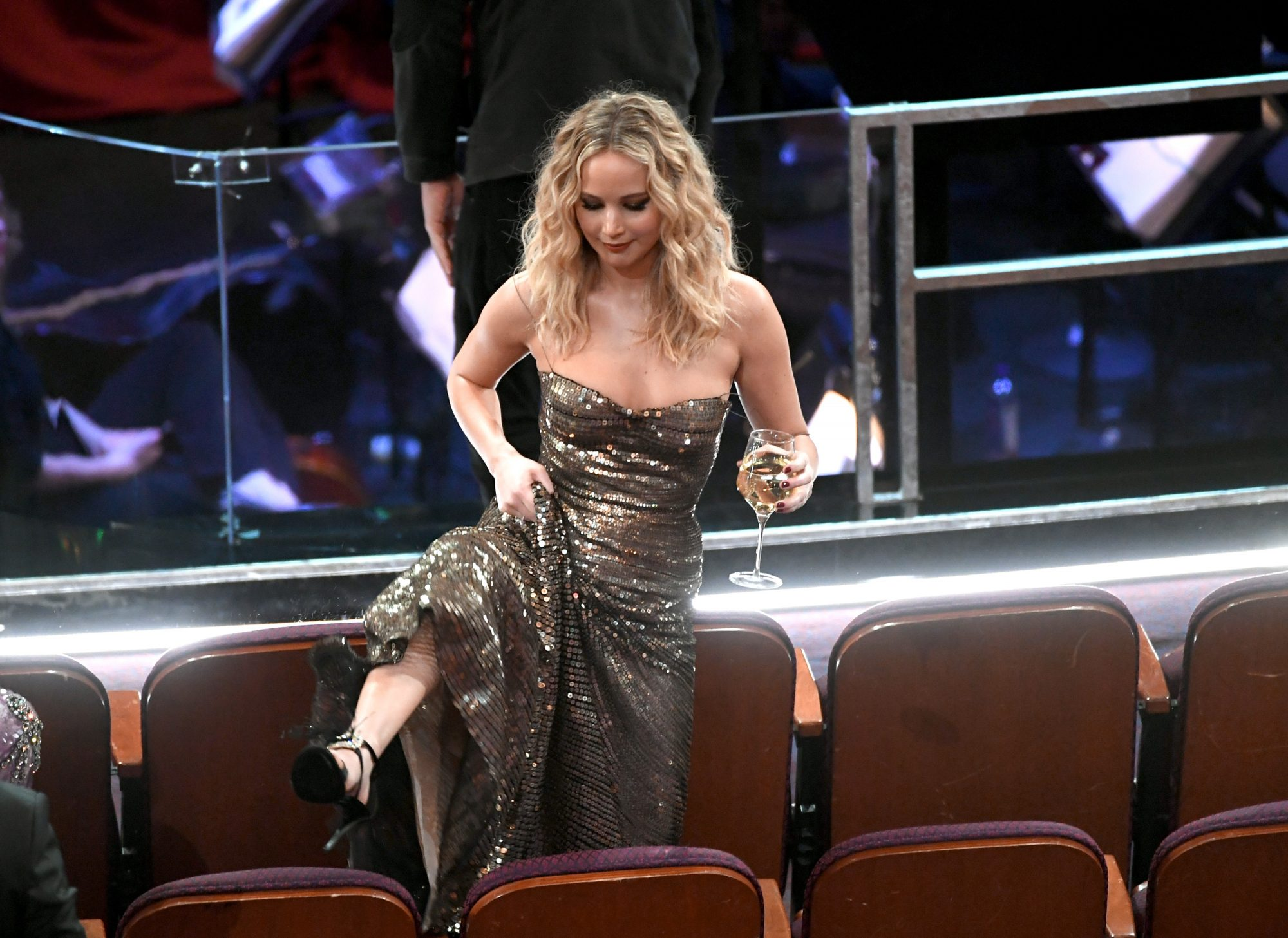 Jennifer Lawrence Is Peak Jennifer Lawrence Climbing Over Chairs at the Oscars, Wine Glass in Hand