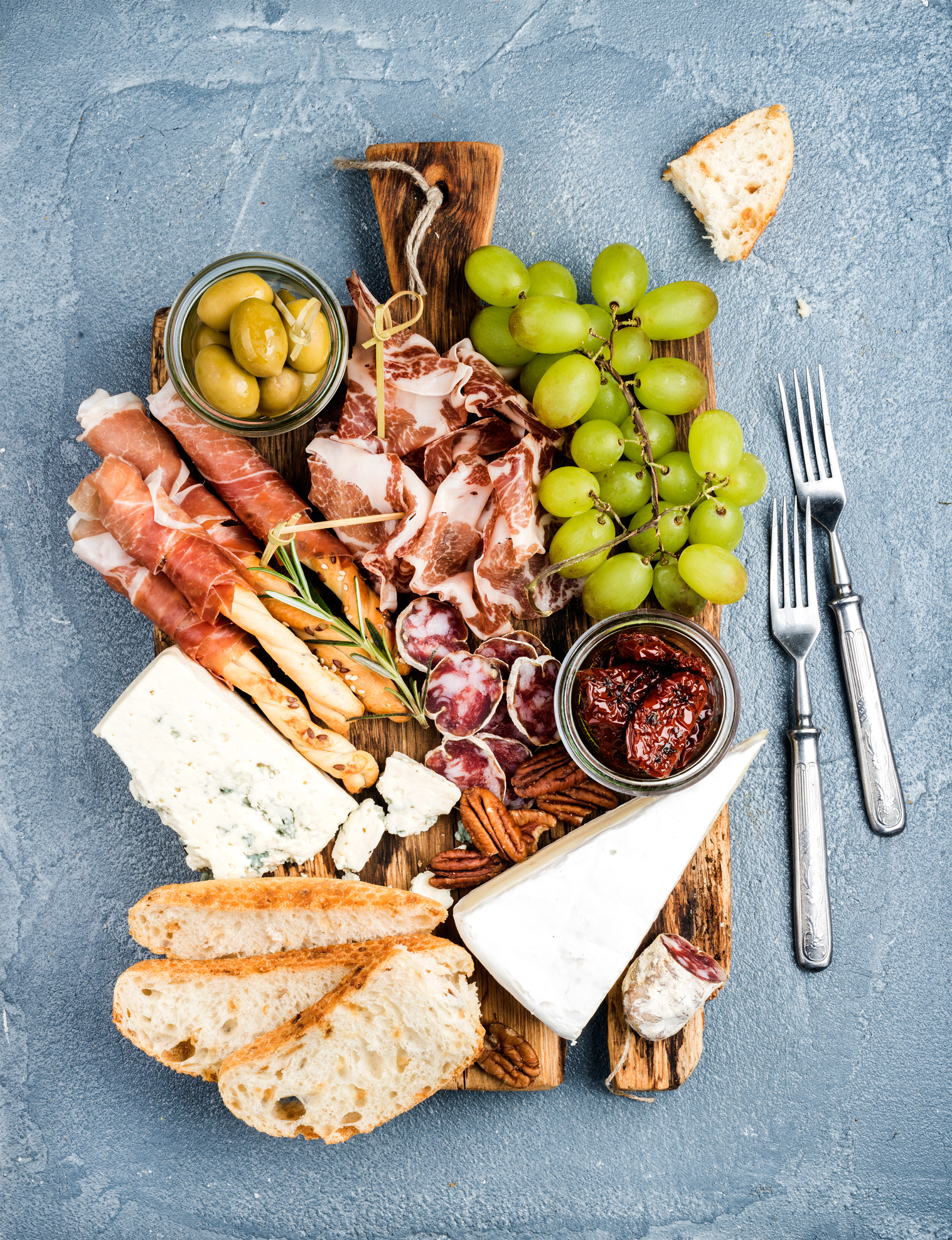 <p>Cheese and meat appetizer selection. Prosciutto di Parma, salami, bread sticks, baguette slices, olives, sun-dried tomatoes, grapes and nutson rustic wooden board over grey concrete textured backdrop, top view</p>