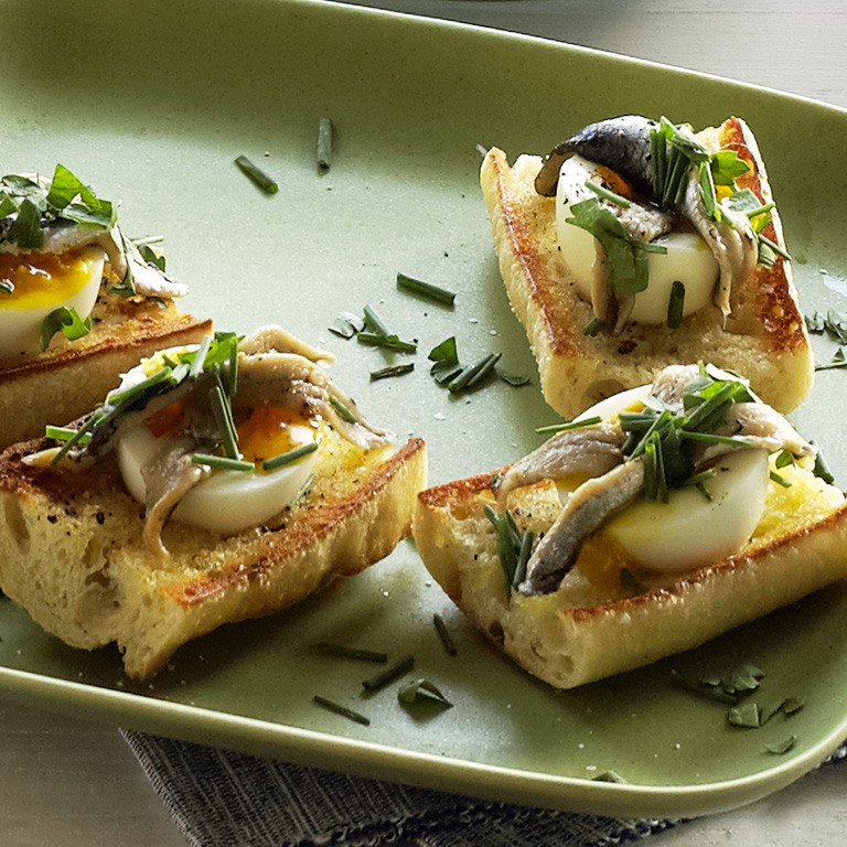 Egg and Anchovy Crostini RecipeEnjoy eggs with soft yolk, nestled into lemon-scented toasts and topped with marinated white anchovies for a fresh, clean appetizer.