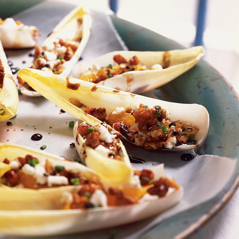 Endive Stuffed with Goat Cheese and Walnuts RecipeEndive leaves make a perfect container for the crumbled cheese, orange sections, and walnuts in this appetizer that's basically a hand-held salad.