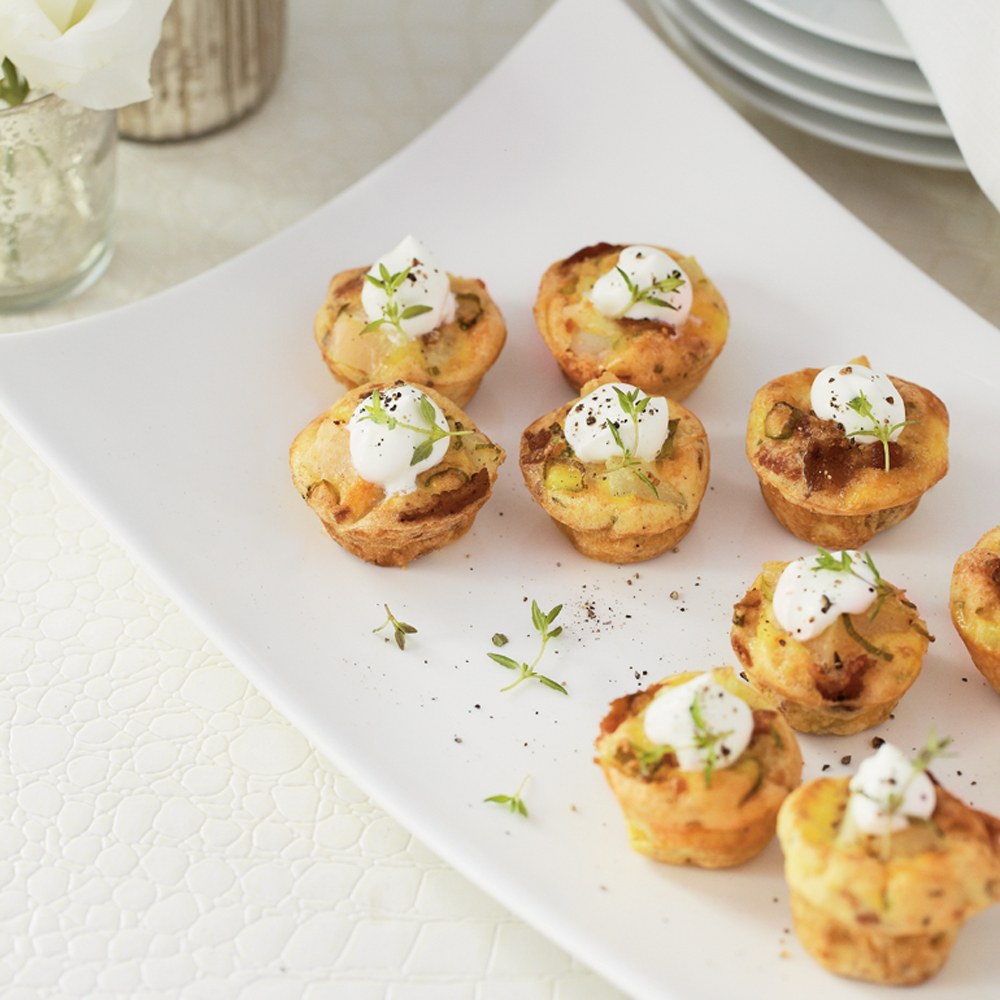 Mini Bacon Quiches RecipeThese mini crustless quiches are filled with potato, bacon, Parmesan cheese and sour cream and baked in mini muffin pans.   You can serve them either warm or at room temperature.