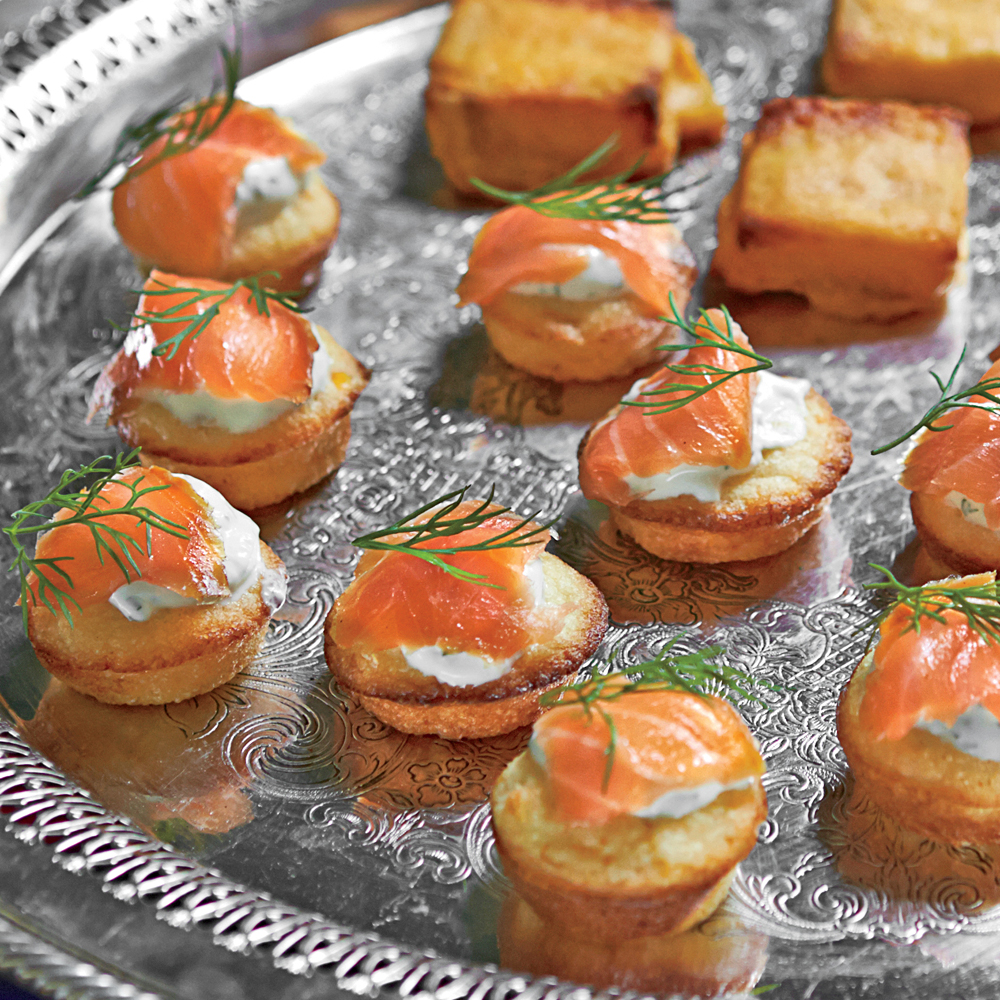 Mini Corn Cakes with Smoked Salmon and Dill Crème Fraîche RecipeMake these in the morning, and top with salmon and crème fraîche just before your guests arrive. Tight on time? Use store-bought blini instead.