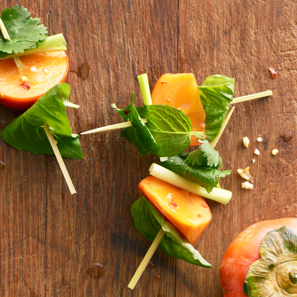 Skewered Persimmon and Herb Bites RecipeThe combination of persimmons with Southeast Asian herbs and dunk sauce comes as a surprise in these quick appetizers, and it's totally addictive.
