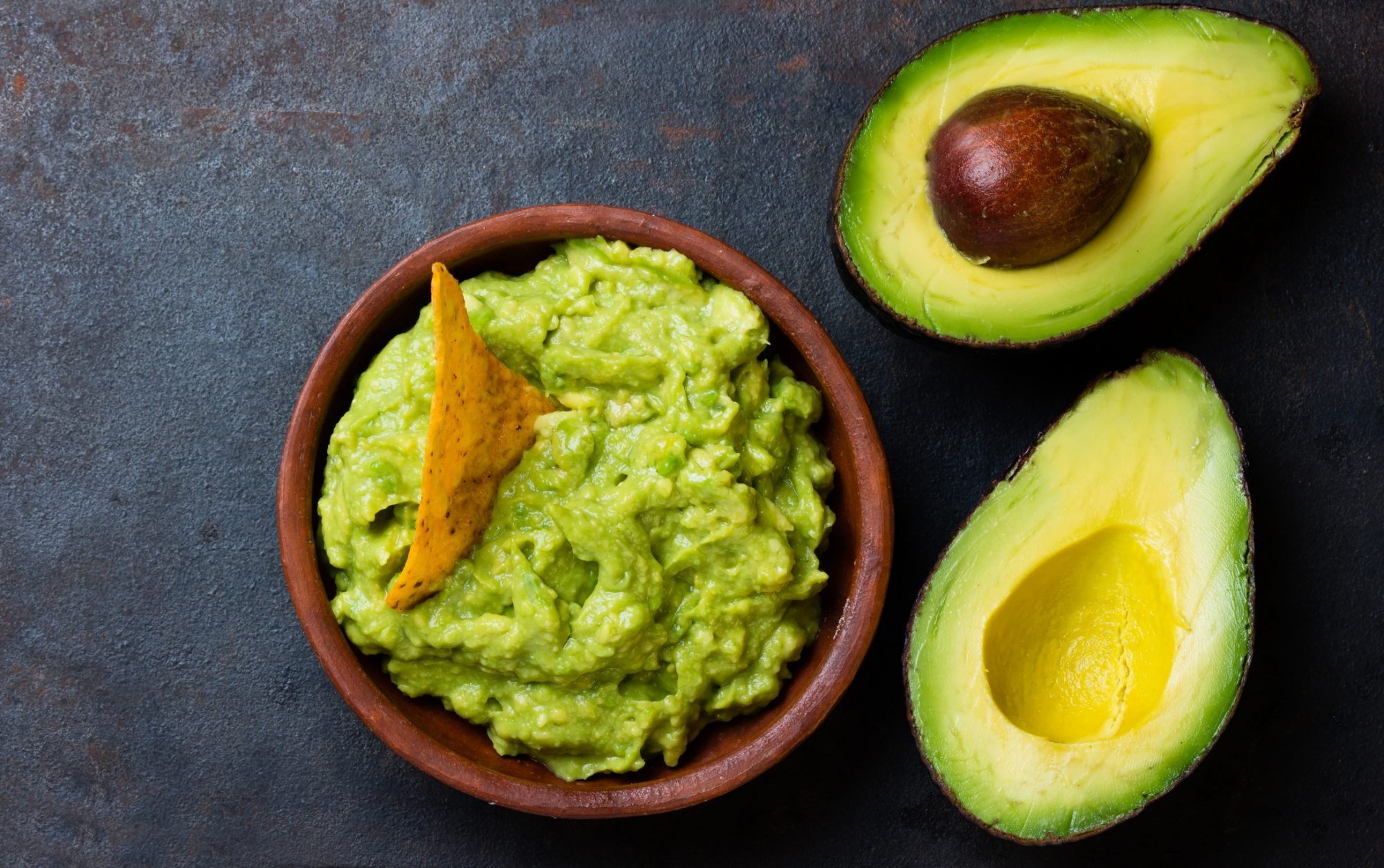 <p>Traditional latinamerican mexican sauce guacamole in clay bowl and avocado sandwiches on dark background. Top view</p>