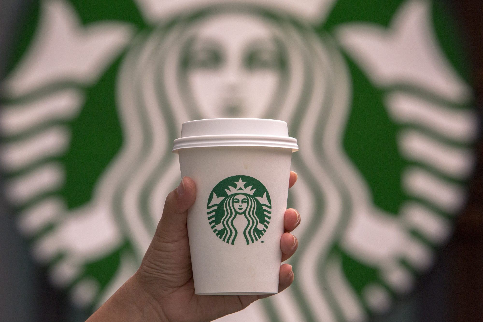 Hand holding a cup of coffee in front of Starbucks logo.