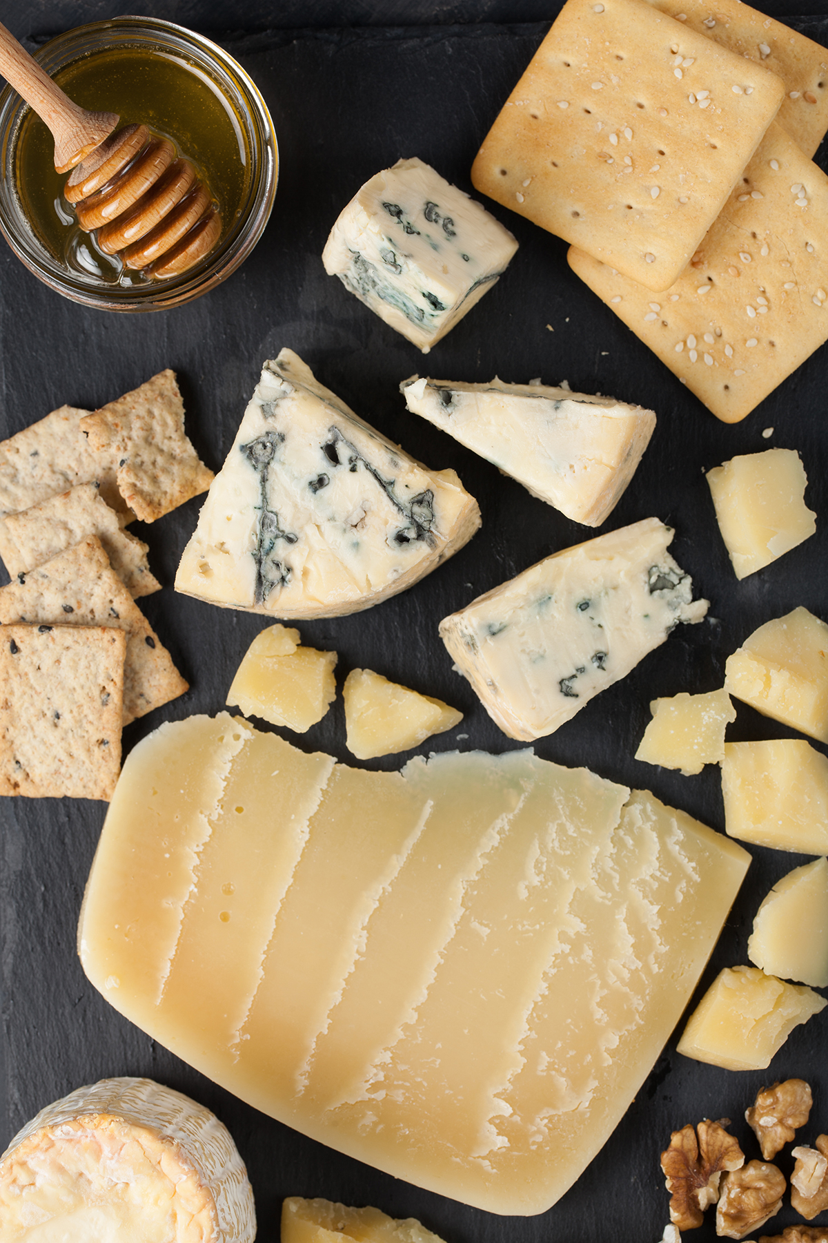 Slate board with cheese, honey, nuts, crackers