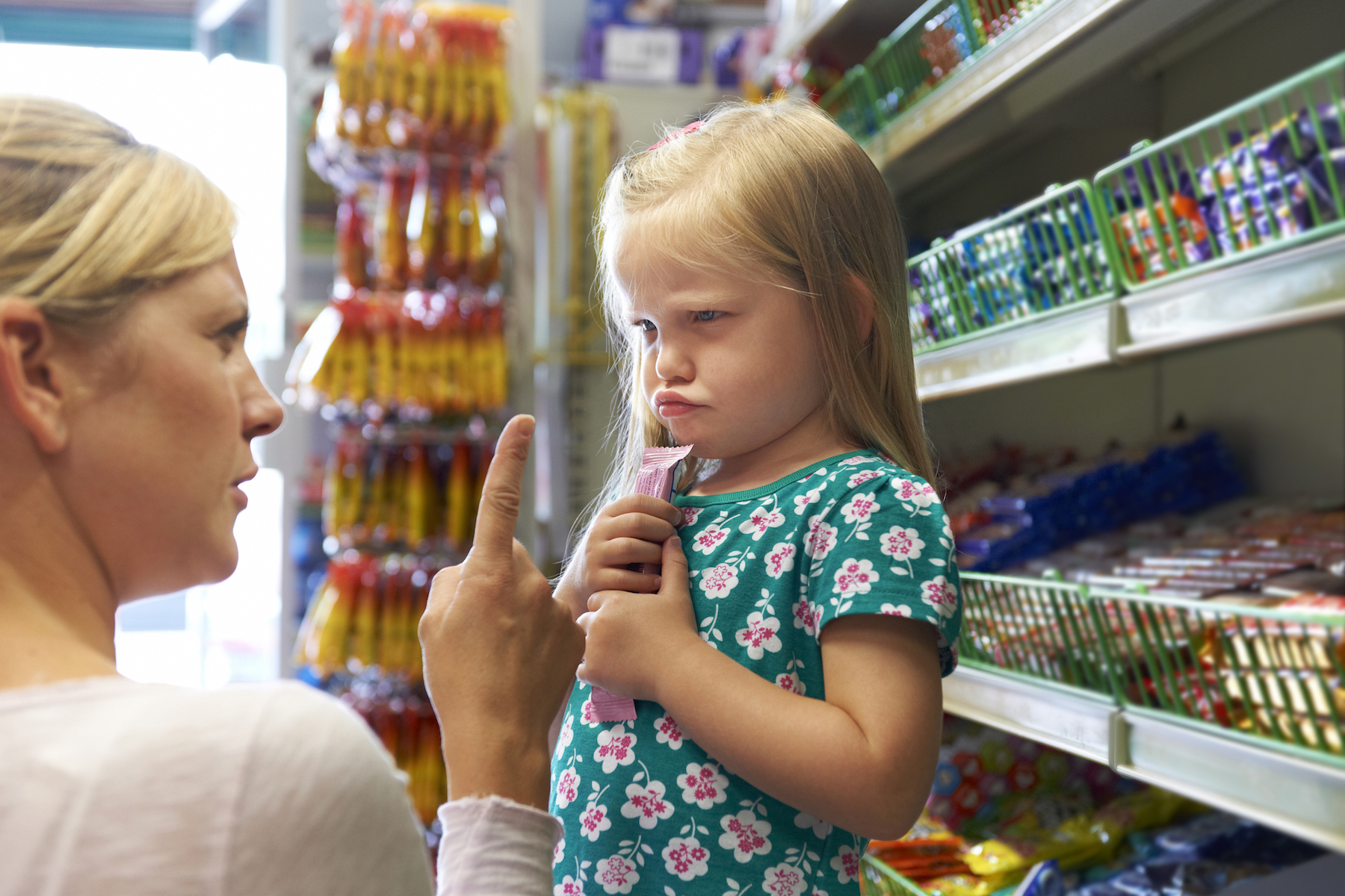 Woman disciplining girl in candy store