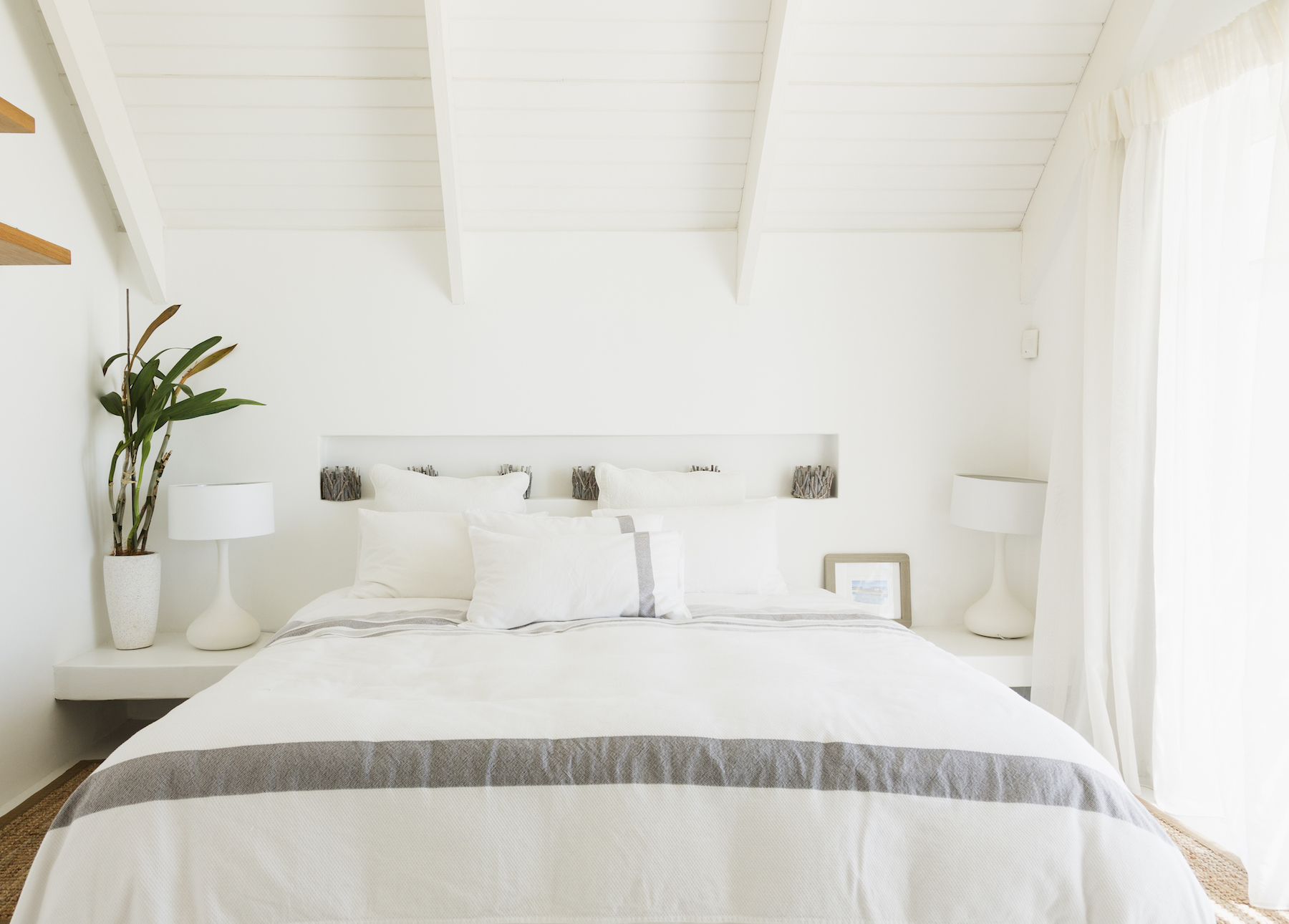 White Minimalist Bedroom with plant, bed, and pillows