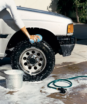A person cleaning a car tire