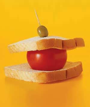 Tomato between two slices of bread, speared by a toothpick with an olive