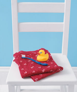 Rubber duck, toothbrush, and towel on a chair