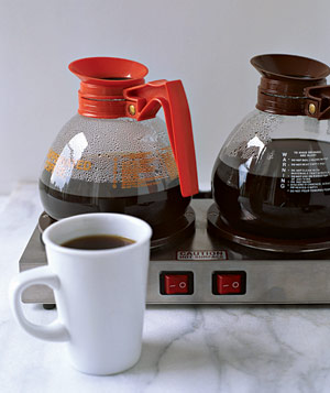 Cup of coffee in front of decaffeinated and regular coffee pots