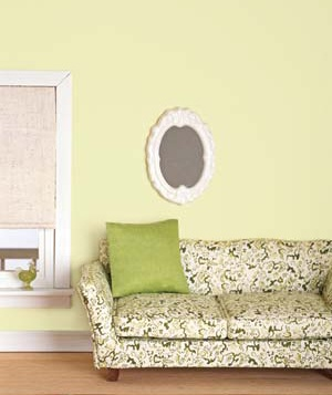 Couch with green pillow and hanging mirror