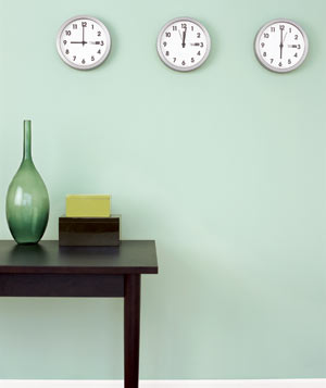 Three clocks in a light green hallway