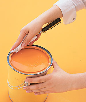 Woman wiping the rim of a paint can
