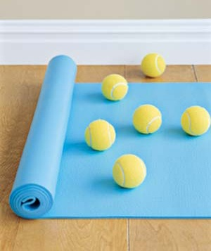 Tennis balls on a blue yoga mat