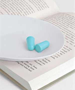 Earplugs resting on a book