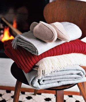 Pile of quilts and slippers on a chair in front of a fireplace