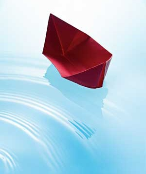 Red origami boat in water