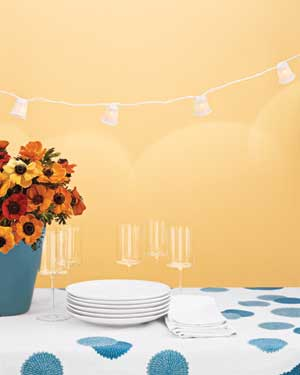Table with plates, glasses, flowers, and lights strung above it