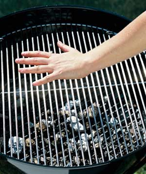 Hand on barbeque grill testing for heat