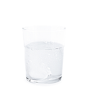 Glass of water with antacid tablet