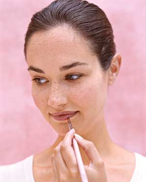 Woman applying lip color with a brush