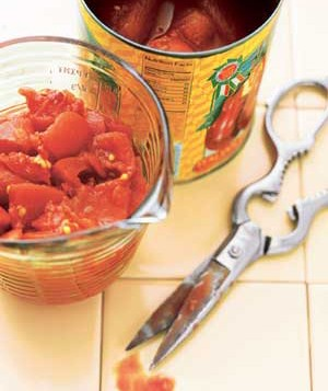 Measuring jar of canned tomatoes and scissors