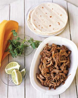 Plate of pulled pork with tortillas and limes