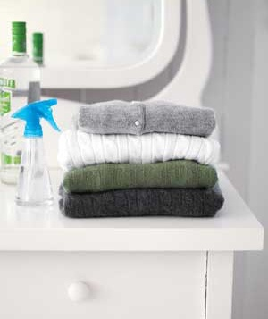 Folded sweaters on a dresser with vodka and a spray bottle