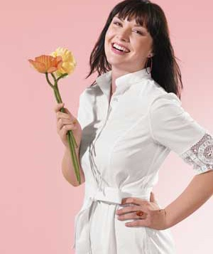 Woman in a white button-down holding a flower