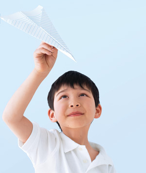 Young boy with paper airplane