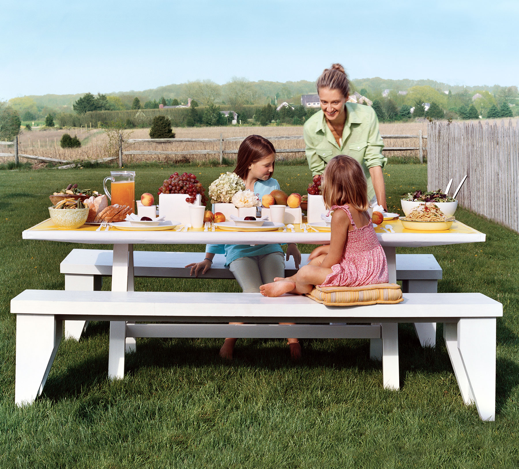 Family eating dinner on a picnic table in the countryside