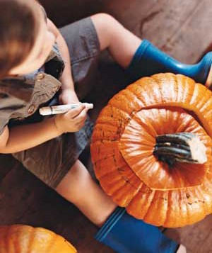 Child decorating a pumpkin