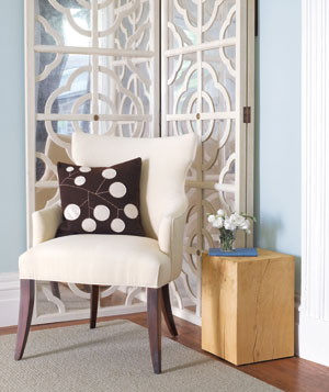 White chair in front of a decorative screen