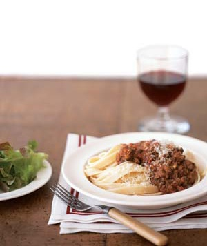 A bowl of Fettucine Bolognese with salad and a glass of red wine