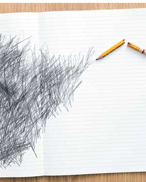 Notepad with scribbles and a broken pencil