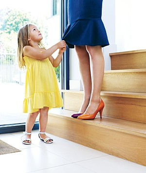Little girl tugging on her mother's skirt