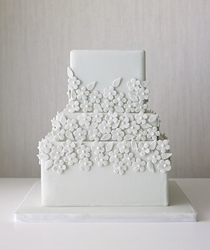 Tiered wedding cake decorated with monochromatic flowers