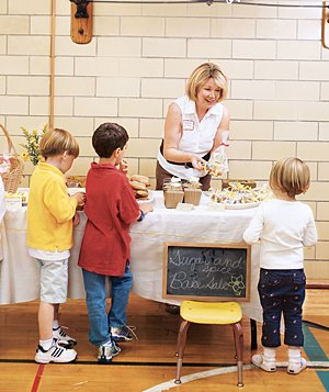 Woman and children at a bake sale