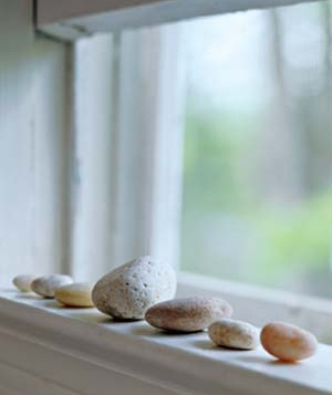 Beach rocks lined up along a windowsill