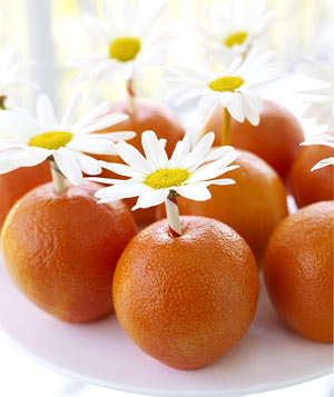Oranges with daisies on a cake stand
