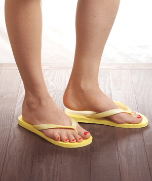 Woman's feet in yellow flip flops