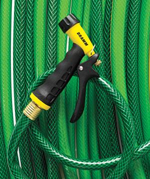 Green gardening hose with yellow spray nozzle