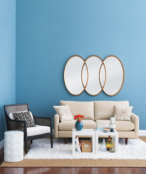Living room with blue walls and large circular mirrors